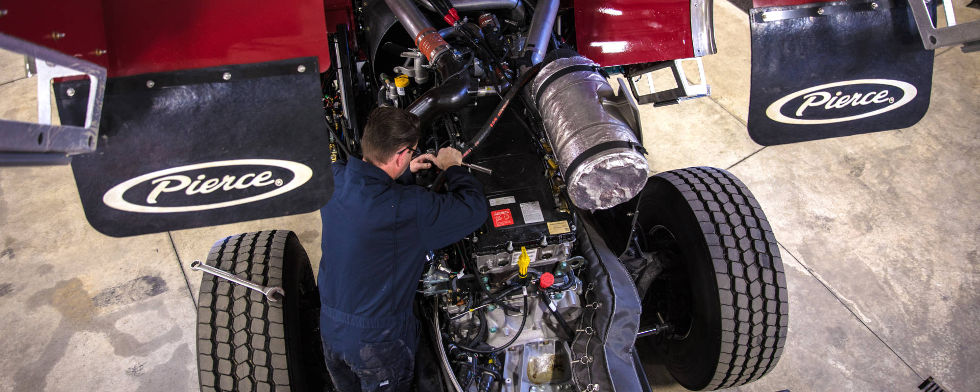 A certified Pierce Mfg. Technician works under a raised cab.